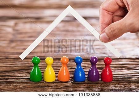 Close-up Of A Person Hand And Multi Colored Person Under Home Roof On Wooden Table