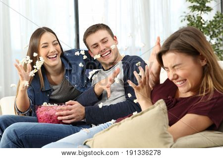 Three happy friends joking and throwing popcorn sitting on a sofa in the living room at home