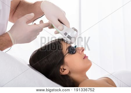 Young Woman Getting A Laser Skin Treatment On Her Forehead In Healthy Beauty Spa Salon