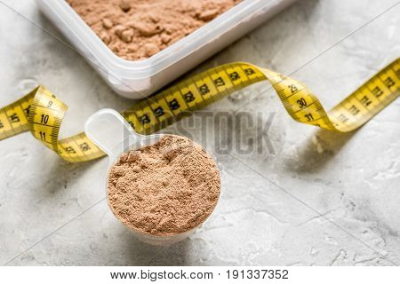 Whey protein powder for fitness nutrition to start training and measure tape on stone background