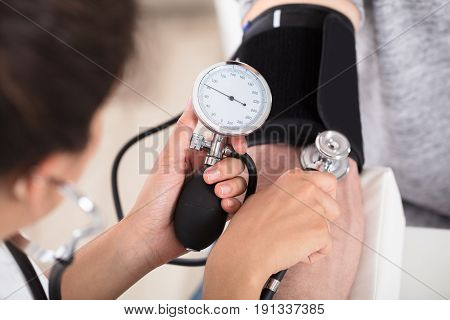 Doctor Cardiologist Measuring Blood Pressure Of Male Patient In Clinic