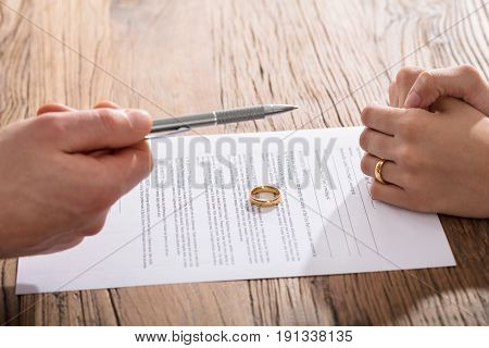 Close-up Of Couple Singing Divorce Agreement With Gold Wedding Ring On Paper