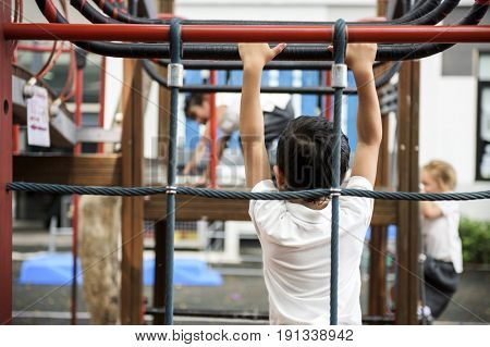 Rear view of young kindergarten boy at playground