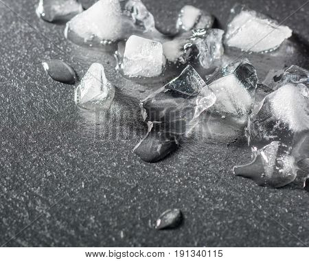 Pieces of crushed ice on a black stone. Drops of water and cold. Dark background.