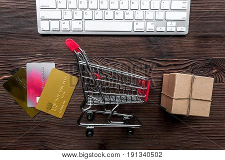 making purchase with credit cards and mini trolley on office desk background top view