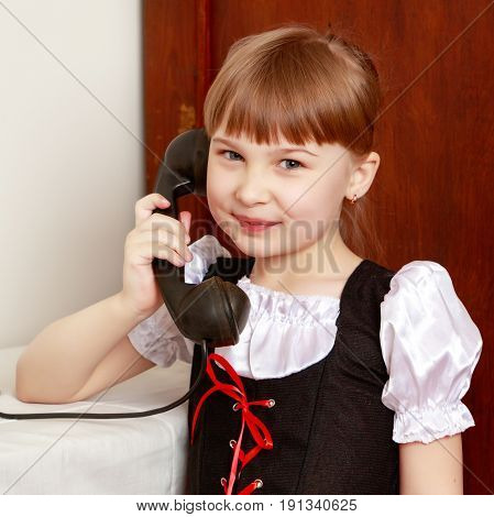 A sweet little blonde with long hair braided in a bun and a short bangs on her head. In a beautiful dress with a white apron.The girl dials the number on the old black phone.