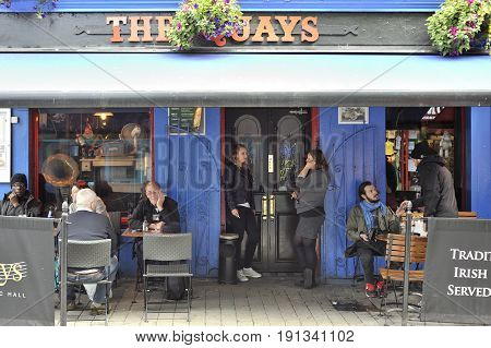 Latin Quarter, Galway, Ireland June 2017, The Quays Bar Main Entrance, Girls Smoking And Some People