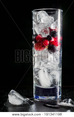 Glass of ice with berry gooseberries red black currants and water. Refreshing cocktail. Summer drink. Dark background.