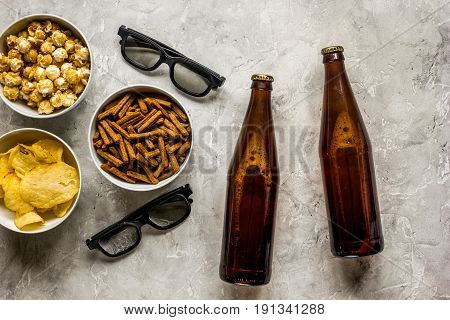 film whatching party with beer, crumbs, chips and pop corn on stone background top view