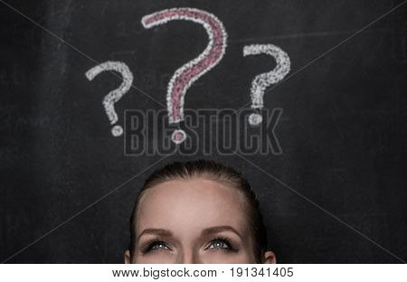 Closeup portrait of young confused woman isolated over black chalkboard with drawn question marks