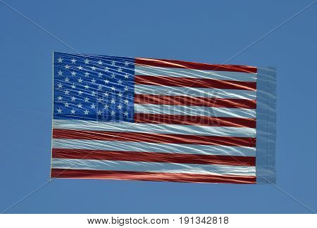 Giant American flag airborne as aerial banner against blue sky