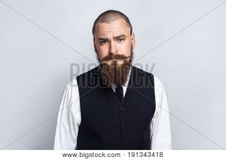 Unhappy. Handsome businessman with beard and handlebar mustache looking at camera with sad unhappy face. studio shot on gray background.