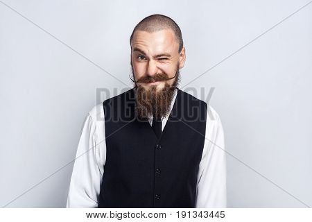 Wink. Handsome businessman with beard and handlebar mustache looking at camera and winking. studio shot on gray background.