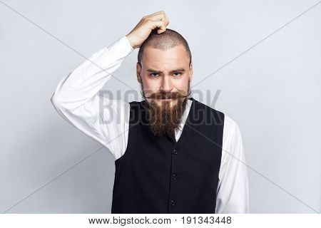 Thoughtful. Handsome businessman with beard and handlebar mustache looking at camera and thinking. studio shot on gray background.