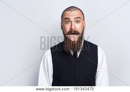 Crazy Funny face. Handsome businessman with beard and handlebar mustache looking at camera with tongue out. studio shot on gray background.