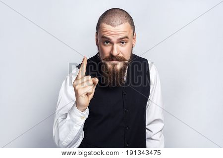 Warning. Handsome businessman with beard and handlebar mustache looking at camera with serious face and finger warning. studio shot on gray background.