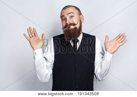 I Dont Know. Handsome businessman with beard and handlebar mustache looking at camera and confused. studio shot on gray background.