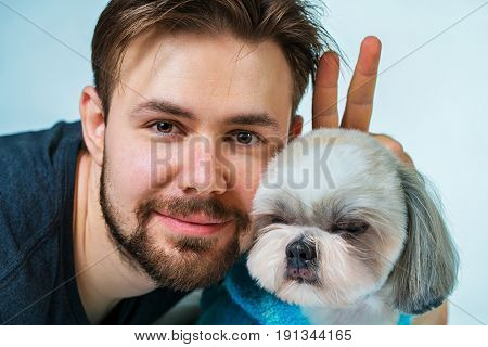 Young man with shih tzu dog portrait. Love and fun concept.