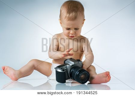 Eight month baby sitting and playing with camera on white background