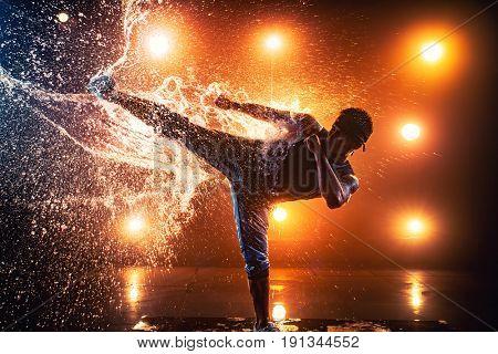 Young man break dancer making kick on splashing water. Tattoo on body.