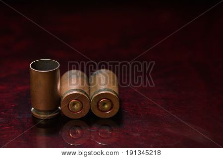 Empty Casings From Bullets Of Small Caliber Gun On A Background Of Red Glass