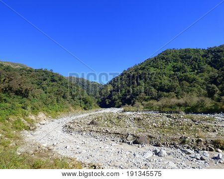 Dry river. At the background, there are mountains with generic vegetation and a cloudless sky. Location: north of Argentina
