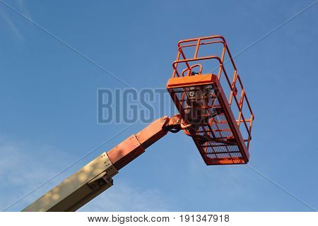Hydraulic boom lift and blue sky with copy space