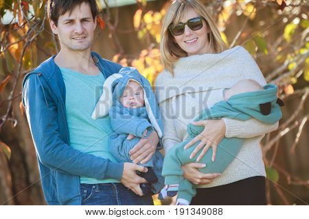 outdoor portrait of young happy smiling mother and father with twin babies on natural background