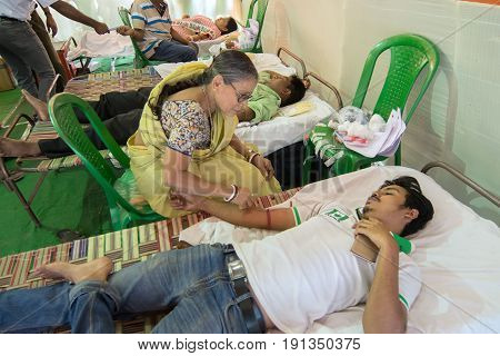 KOLKATA INDIA - MARCH 19 2017 : Old woman collecting blood from young male volunteer lying on bed inside public blood donation camp. Blood will be preserved for future use by other needy people.
