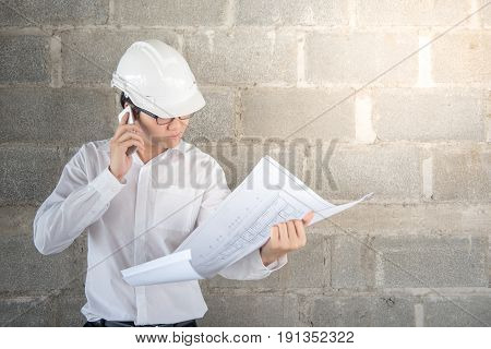 Engineer or Architect with protective safety helmet checking architectural drawing and calling support team at construction site. Engineering Architecture and building construction concepts