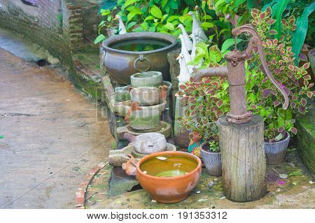 Old hand water pump and clay bowl at outdoor.