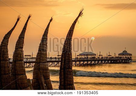 The sunset with traditional boat craft at Huanchaco town near Trujillo Peru