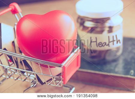 Red heart in shopping cart with money saving for healthcare or medical assurance concept