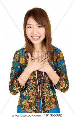 Portrait of young southeast Asian woman in traditional Malay kebaya dress greeting, standing isolated on white background.