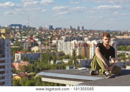 The roofer rests after climbing to the roof. Active way of life in urban space. Courage and adrenaline.