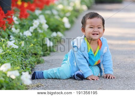 Asian boy is happily on the corridor in flower gardenconcept Learning and health of the baby.