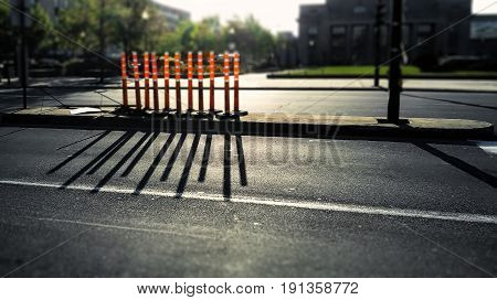On a bight summer evening. Eleven orange construction cylinders casting shadow on the asphalt. Blurry background.