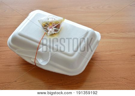 ready meal packing in foam box with plastic spoon and chili fish sauce