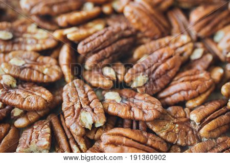 Closeup on shelled pecans. Background of organic pecan nuts selective focus