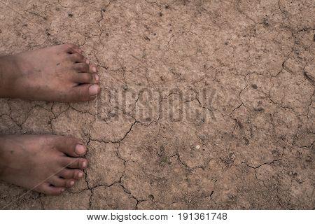 Children feet on the arid soil background