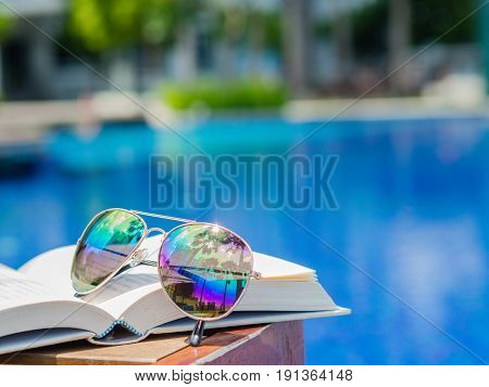 sunglasses on open book at the side of swimming pool. Vacation beach summer travel concept