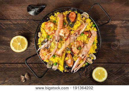 A photo of a Spanish seafood paella in a typical paellera, with mussels, clams, shrimps, and lemon wedges, shot from above on a dark rustic texture with lemons and shells, with a place for text