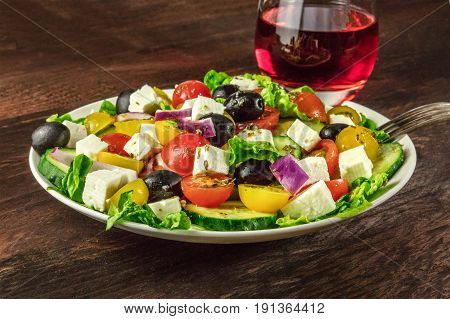 A photo of a plate of Greek salad, with feta cheese, fresh vegetables, and olives, with a glass of rose wine and a fork, on a dark rustic texture with a place for text