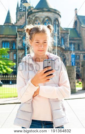 Smiling young beautiful girl using mobile smartphone in Glasgow historical place. Traveling. Summertime multicolored outdoors vertical image.