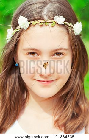 Looking at camera boho style girl with floral headband on head and butterfly on nose. Summer outdoors.