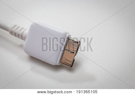 White usb 3.0 cable with micro B connector on white background close up image