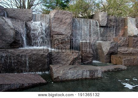 Horizontal image of several rocks with water flowing over them, a peaceful place to sit and think.