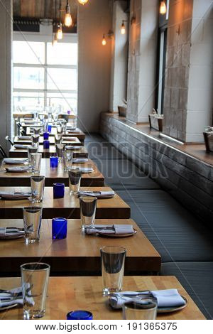 Vertical image of wood tables set for dinner, with bright blue glasses and  welcoming atmosphere.