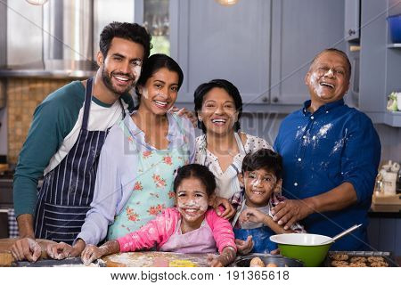 Portrait of cheerful multi-generation family enjoying while preparing food in kitchen at home