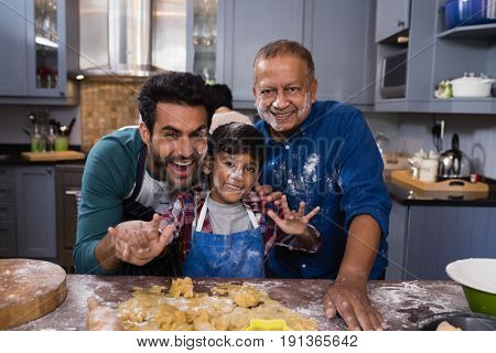 Portrait of happy multi-generation family standing together by dough in kitchen at home